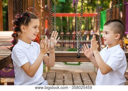 Happy Lovely Boy And Pretty Girl Sitting And Clapping Hands At The Playground. Concept Of Summer, Ch