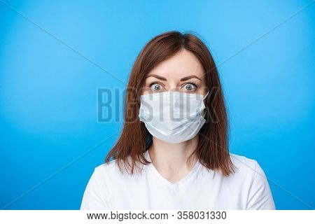 Surprised Woman In Aseptic Mask. Light Blue Background