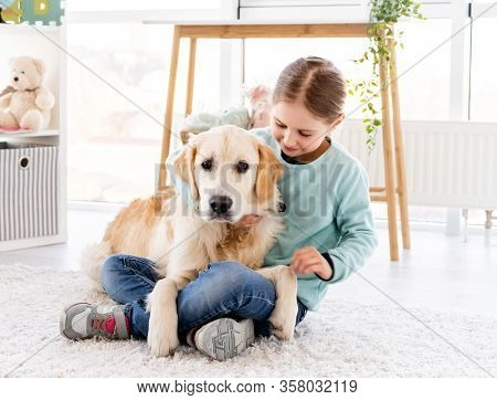 Happy little girl holding adorable golden retriever at home