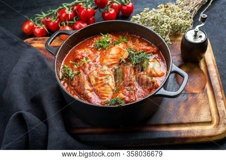 Traditional Brazilian fish stew moqueca baiana with fish filet in tomato sauce as closeup in a modern design cast-iron roasting dish