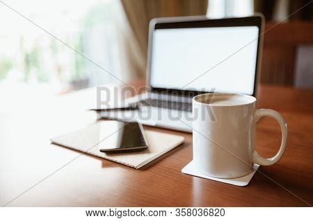 Home Office Desk.white Cup Of Coffee With Laptop And Smart Phone On Wooden Table, Midday Light Comes