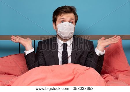 Man In Medical Mask Sitting In Bed Being Unsure In Future.