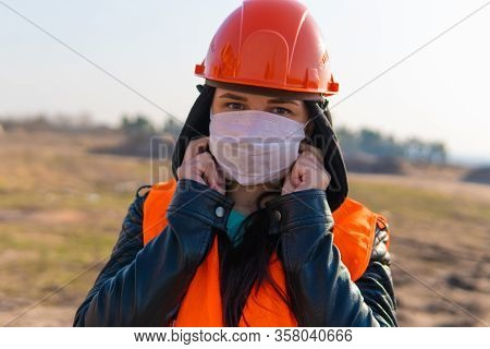 Female Construction Worker In Overalls Putting On Medical Mask On Face On Construction Area.