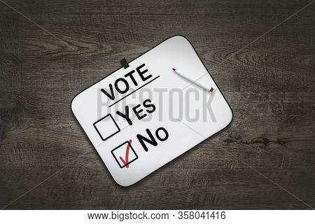 White Board With The Word Vote,yes  And No Check Boxes ,on A Dark Wooden Background
