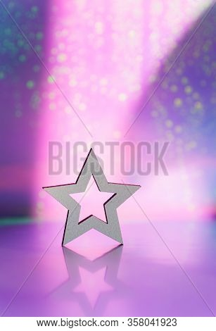 Wooden Icon Of White Star With Hole On Pink And Purple Blurred Galactic Background With Light Bokeh.