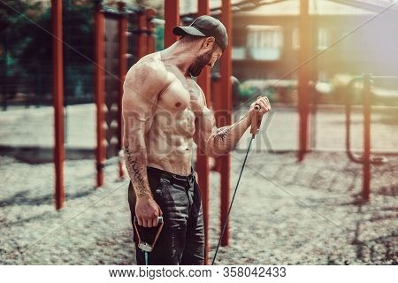 Fitness Man Exercising With Stretching Band. Muscular Sports Man Exercising With Elastic Rubber Band
