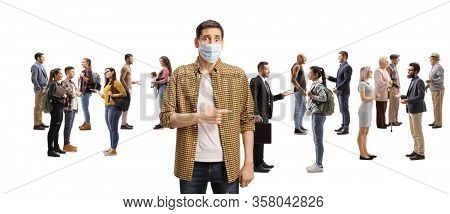 Worried youn man with a medical face mask pointing to a large group of people talking isolated on white background