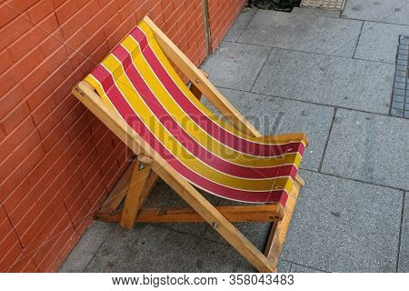A Wooden Folding Chaise Longue With A Striped Fabric Stands Along A Street In Batumi, Georgia. Old C