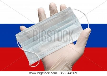 Doctor Holds Face Mask In Hand In White Medical Gloves On Background Colors Flag Of Russia. Concept