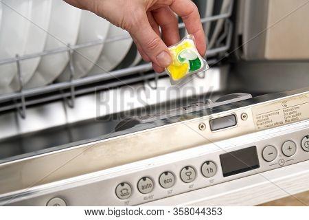 Putting Tab Into Full Dishwasher Close Up. Integrated Dishwasher Machine Full Loaded. Woman Hand Hol
