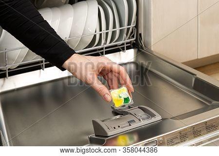 Putting Tab Into Full Integrated Dishwasher Close Up. Dishwasher Machine Full Loaded. Woman Hand Hol
