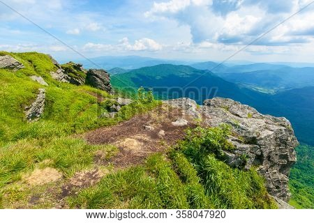 View In To The Valley From The Top Of A Mountain. Huge Rocks On The Grassy Hillside. Clouds On The S