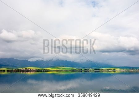 Lake In Mountains. Cloudy Day In Springtime. Great Scenery Of High Tatra Mountains In Dappled Light.