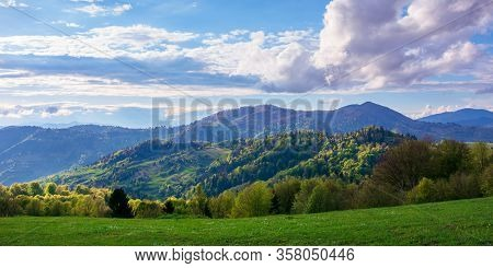 Beautiful Rural Panorama In Mountains. Fields And Meadows On Hills Rolling In To The Distant Ridge.