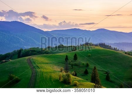 Mountainous Countryside In Springtime At Dusk. Road Among The Trees On The Rolling Hills. Ridge In T