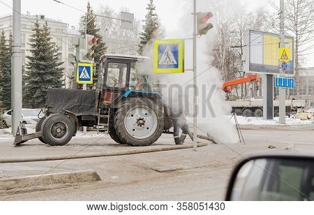 A Tractor Of The Municipal Social Service Stands On A City Street Against The Background Of Passing