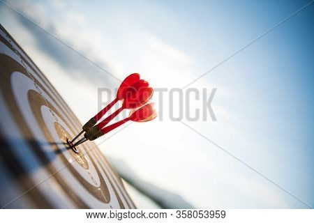 Close Up Shot Red Darts Arrows In The Target Center On Dark Blue Sky Background. Business Target Or
