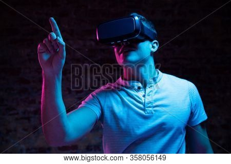Front view of a Caucasian man with short hair wearing a Virtual Reality headset and touching a virtual interactive screen with his finger, lit with pink and blue light on a black background.