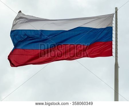 Russian Flag Flying On A Flagpole In A Strong Wind. Symbol Of Patriotism. Tula, Russia