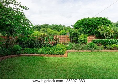 Beautiful English Cottage Garden, Colorful Flowering Plant On Smooth Green Grass Lawn With Orange Br