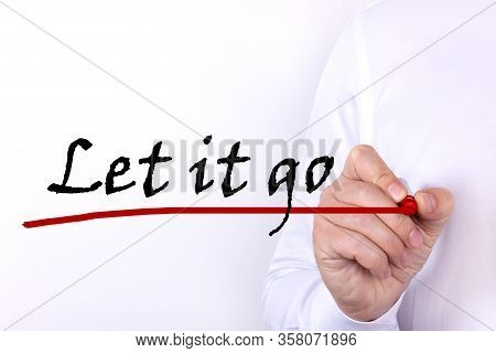 A Person Writes A Word, The Phrase Let It Go With Marker On A Light Background. Business Concept.