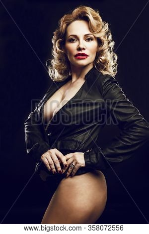 Beautiful Sexy Adult Blond Woman In A Leather Jacket Worn On Her Naked Body. Black Background. Verti