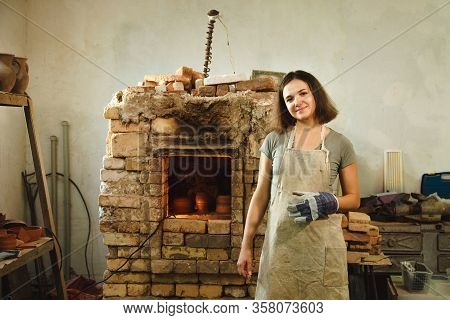 Potter Girl Smiling In Workshop On Background Of Brick Oven. Female Mastery Concept With Copy Space.