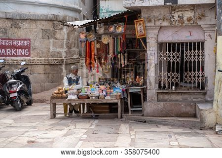 Eklingji, India - March 15, 2020: Vendor Sits At His Market Stall Stand, Selling, Books, Trinkets An