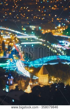 Tbilisi, Georgia. Abstract Blurred Bokeh Architectural Urban Backdrop Of Sioni Cathedral And Bridge
