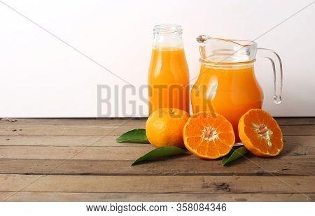 Jug Of Orange Juice On Wooden Table