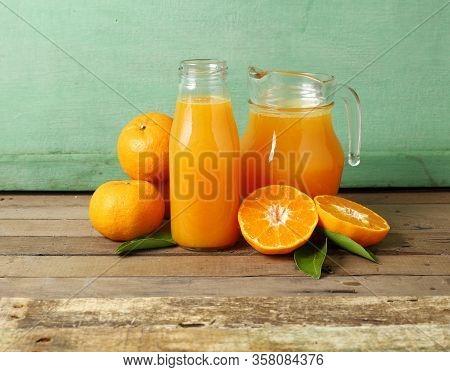Fresh Slice Orange And Bottle Of Juice On Wooden Background