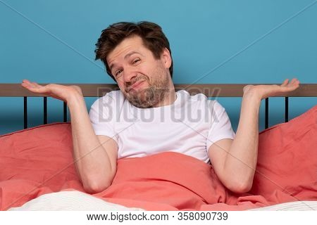 Confused Caucasian Man Is Unsure In Bed Shrugging Hands.