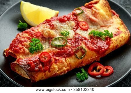Baked Chicken Fillets Enchiladas With Courgette, Salsa Sauce And Cheese Served With Lemon Wedges And