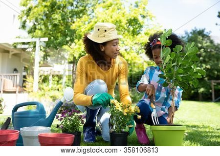 Front view of an African American woman and her daugther in the garden, kneeling and potting plants. Family enjoying time at home, lifestyle concept