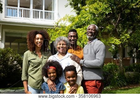 Portrait of a multi-generation African American family in the garden, standing together in the sun smiling to camera. Family enjoying time at home, lifestyle concept