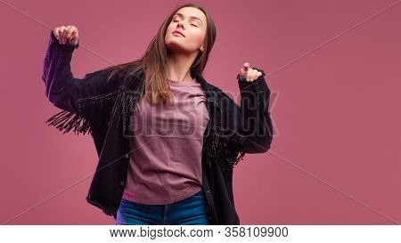 Young Brunette Woman On Pink Background. Studio Portrait, Informal Style Of Clothing, Jeans And A Co