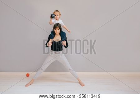 Purposeful Mother Trying Workout At Home. Sport With Child On Her Neck Ready To Doing Lounge Exercis
