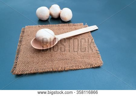 One White Champignon In A Wooden Spoon On A Brown Napkin, On A Gray Background Three Champignons