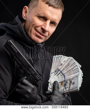 Man In Black Hoody With A Gun And Pack Of Dollars