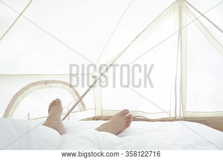 Close The Barefoot Man On The Bed Over The White Blanket And Sheets In The Hotel Bedroom. The Concep