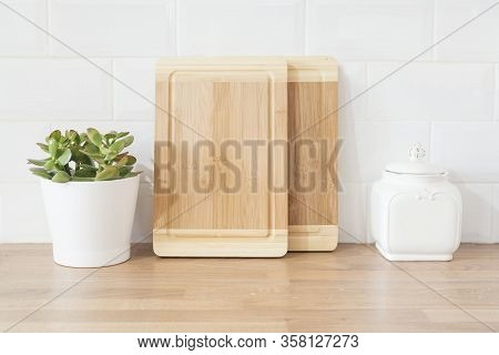Bright And Clean Modern Minimalist Kitchen, Close Up. Cutting Boards, Green Succulent Pot On A Woode
