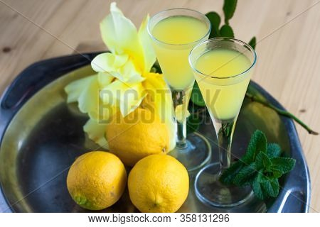 Limoncello In Elegant Liquor Glasses With Lemons, Mint And Yellow Rose On Steel Plate On Wooden Tabl
