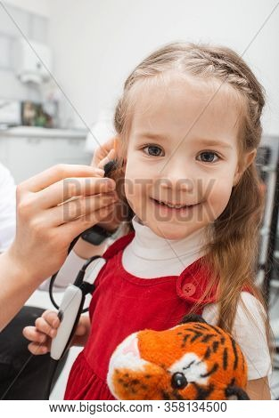 Tympanometry For Child. Hearing Testing For A Little Girl Patient Using Modern Diagnostic Methods.