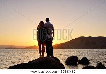 Young couple standing arm in arm, looking at the sunset by the sea