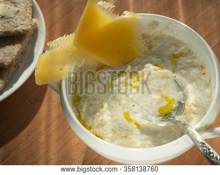 Milk Porridge With Vegetable Oil. Spoon In A Plate With Porridge. On The Porridge Lies Chopped Chees