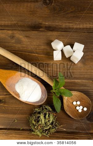 Various forms of stevia natural sweetener plus real sugar lumps on a wooden table
