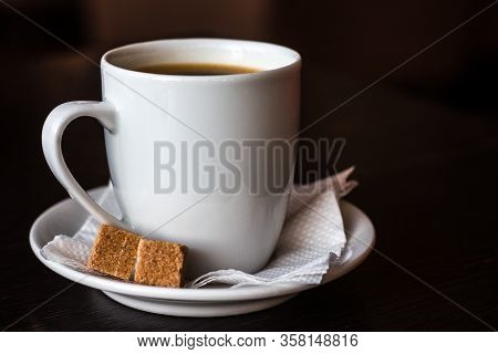 Black Coffee In A White Cup And Saucer. On A Saucer Are Two Pieces Of Cane Sugar. Dark Background.