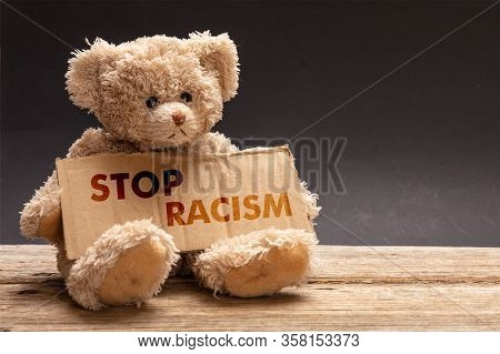 Stop Racism. Poor Homeless Child Begging. Teddy Bear Holding A Cardboard Sign. No To Racism Message