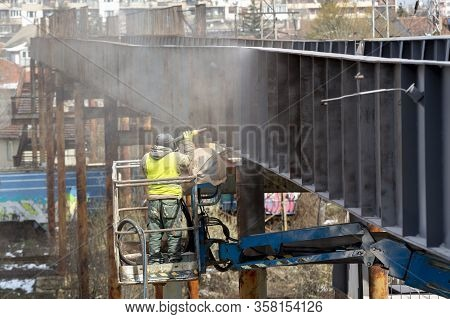 A Worker In Protective Work Wear Incluing Gas Mask Sprays Overpass With Anti Rust Primer.