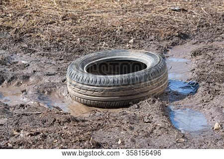 A Worn Car Tire Is Wallowing In Mud And A Puddle On The Ground. Environmental Pollution. Ecological